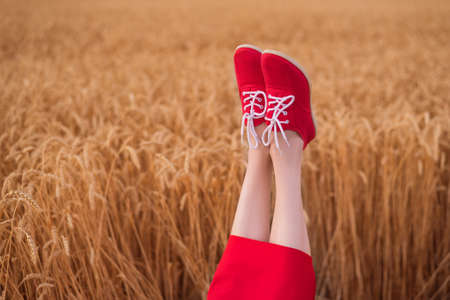 Woman feet up in red shoes funny sticking out of on wheat field background