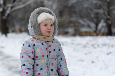 Portrait of little girl in overalls against the background of winter landscape