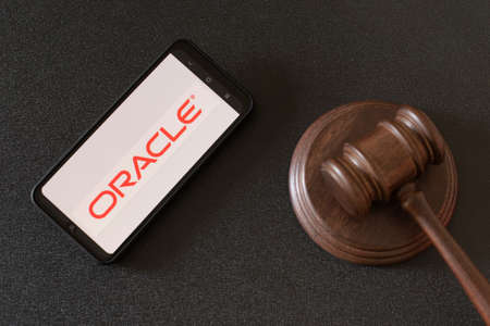 KHARKIV, UKRAINE - JUNE 25, 2020: Oracle logo visible on the phone screen next to judges gavel. Top view.