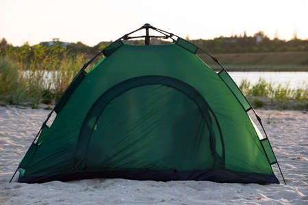 Green tourist tent on the river bank. Tourist equipment.