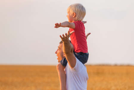Child sits on fathers shoulders and hands up. Happy fatherhood.