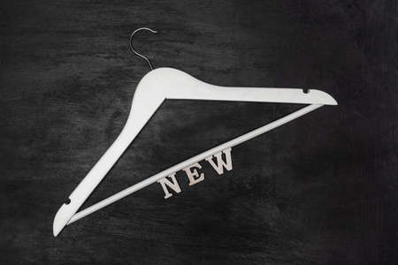 White wooden hanger with inscription new on black background. Updating wardrobe concept. Buying new clothes
