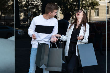Young loving couple carrying shopping bags and laughing. Mock up. Black Friday. Shopping. Consumerism.