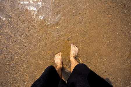 short wave: Mans feet on the sand in the river Stock Photo