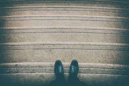 Black shoes on staircase look down. Representing disappointment or regression Stock Photo