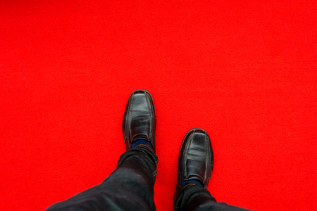 mans shoes standing on red carpet
