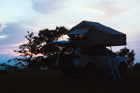 A car with a tent on the roof, parked at top mountain in the evening.