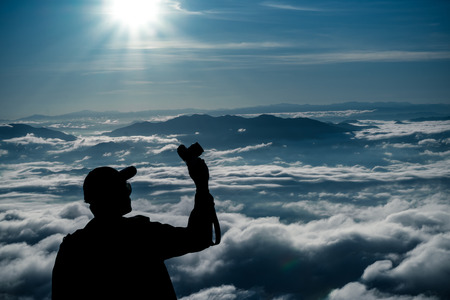 tourist man hold camara with sunrise and sea of fog view on phu chi fa mountain area and national forest park in chiang rai, Thailand. Banco de Imagens