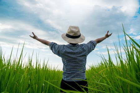 The back of a rural woman raising her hand to the sky