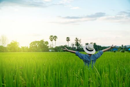 Behind the farmer womans hands raised in the sky in a field with sky background
