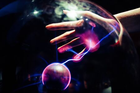 A plasma ball that is releasing electricity on the hand