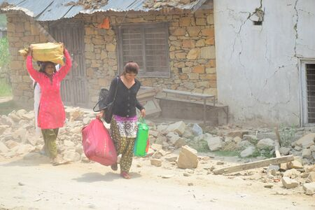 quake: Sipaghat bazar Kavreplanchok district Nepal  May 8 2015 :Women walk in collapsed building after earthquake disaster
