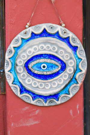 glass turkish evil eye on red door. photo