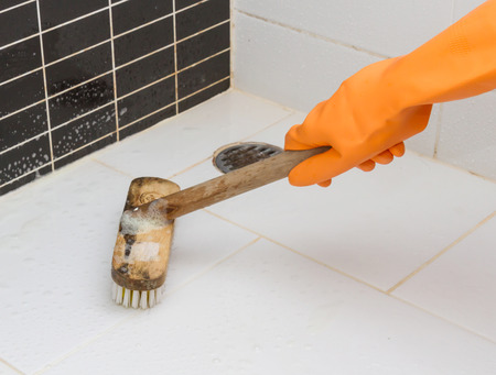 Hand in orange glove cleaning  bathroom dirty floor with brush.