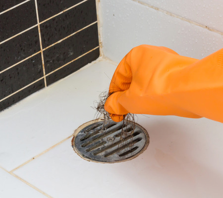 Cleaning bathroom  hair clogged with orange gloves. Stock Photo