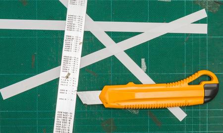 matt: Green cutting mats with iron ruler and yellow cutter.