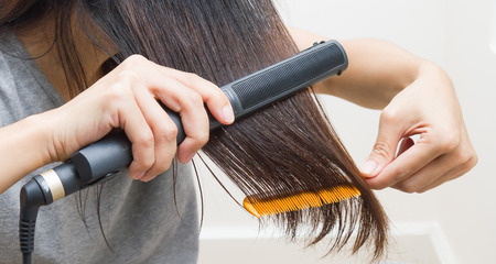 Woman straightening hair with straightener on right hand and comb on left hand. Stock Photo
