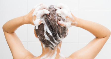 Woman washing her hair on white tiles background. photo