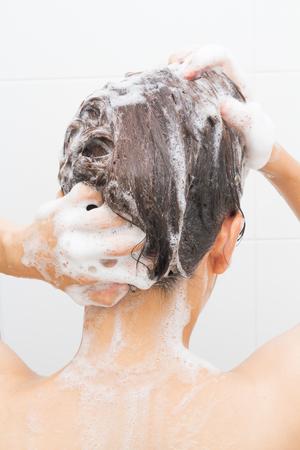 Vrouw die haar haar op witte tegelsachtergrond wast.