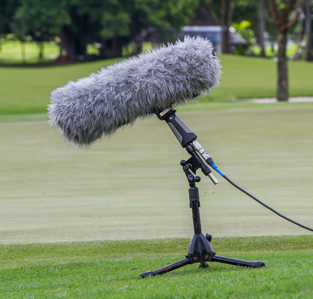 commentators: A large microphone boom with stand for TV or Radio situated at the grass.