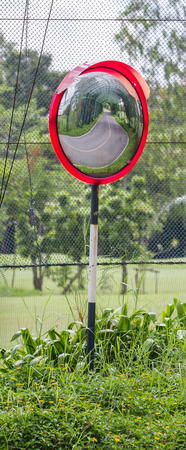 convex: Close up traffic convex mirror on side road near golf course.
