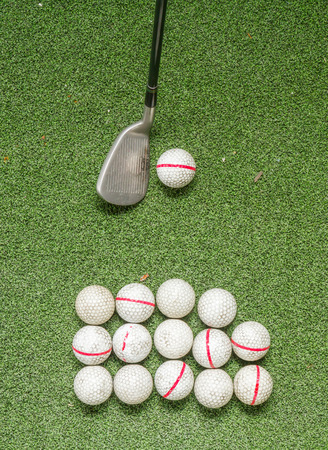 driving range: Old golf balls and iron on artificial grass in driving range for swing practice. Stock Photo