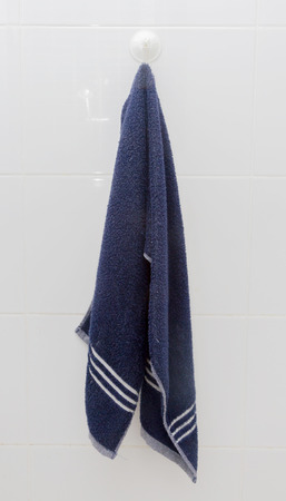 Hanging Blue Towel at suction cup hook on white tile Wall in the Bathroom Standard-Bild