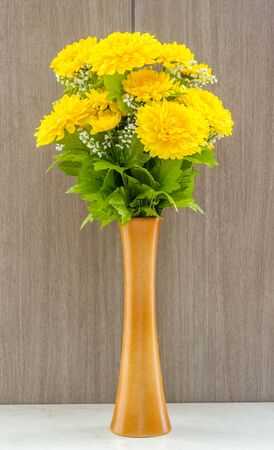 Fake yellow flower in vase at table marble on wooden background.