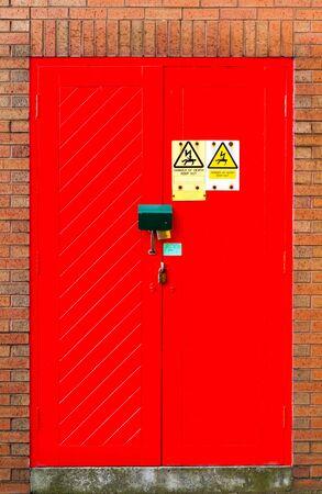 Danger, Red door double lock on brick wall. Standard-Bild - 144221466