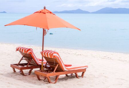 Two orange bed and umbrella on the beach.