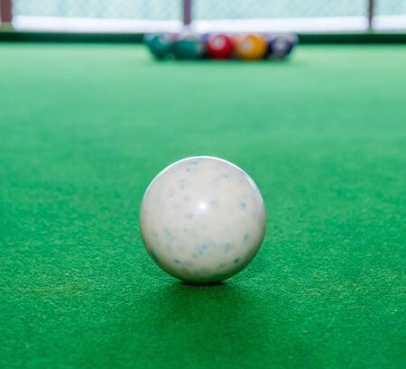Close up, white snooker ball on green table.