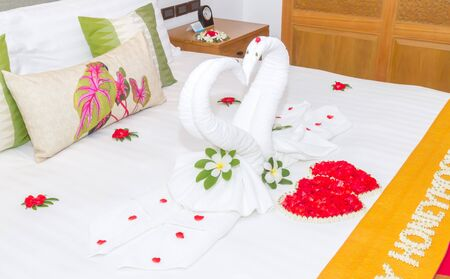 Bedroom design with swans from the towel decoration on bed.