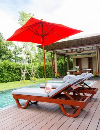 Two beds near the pool with orange umbrella in spa. Standard-Bild