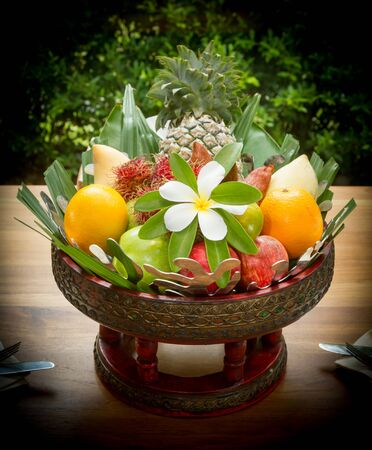 Thai style, Basket fruits on the table decoration with leelawadee flower. Standard-Bild