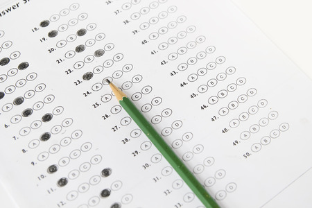 Standardized test form with answers bubbled in and a pencil, focus on anser sheet photo