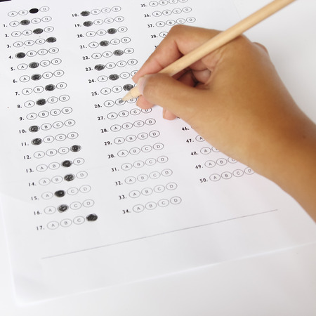 Standardized test form with answers bubbled in and a pencil, focus on anser sheet