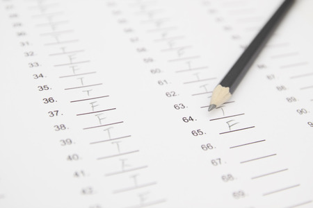 standardized: Standardized test form with answers bubbled in and a pencil, focus on anser sheet