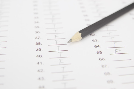 standardized: Standardized test form with answers bubbled in and a pencil, focus on anser sheet and pencil Stock Photo