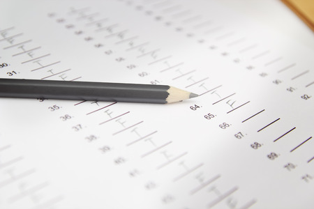 standardized: Standardized test form with answers and a pencil, focus on anser sheet and pencil
