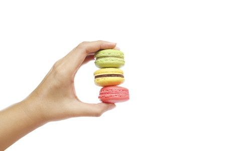 colorfu: female hand hold colorfu ofl macaroons  on white baclground Stock Photo