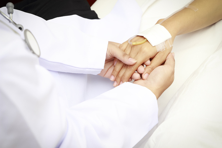 comforting: doctor holing patients hands and comforting her