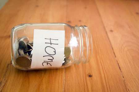 Money in glass jar with home label, financial concept.