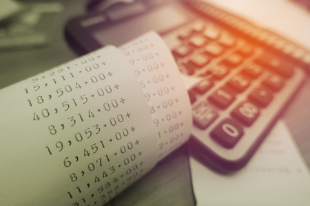 Grocery shopping receipt and calculator on wood table