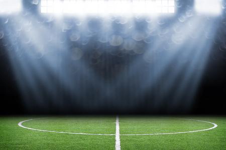 Soccer ball on field in stadium at night