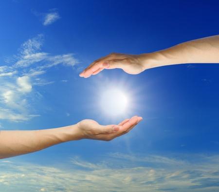 renewabel: hand sun and blue sky with copyspace