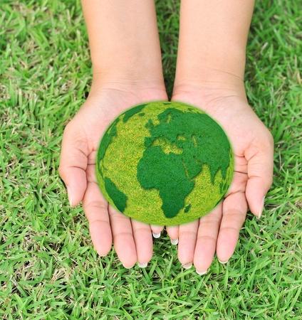 el mundo en tus manos: Mapa del mundo en sus manos con el fondo cubierto de hierba verde