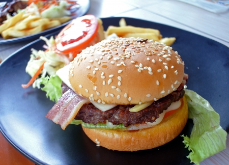 Big appetizing fast food sandwich with lettuce, tomato, smoked ham and cheese . Junk food hamburger.  photo