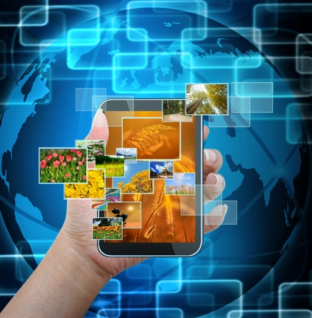holding mobile smart phone with world technology background photo