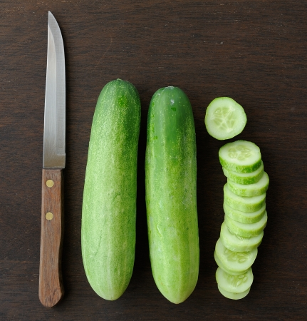 rustical: cucumber slices and  Knife on wooden background