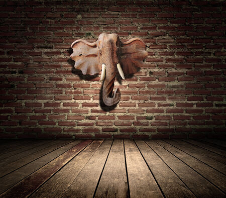 elephant head: room interior vintage with brown textured wall and Elephant head carving Stock Photo